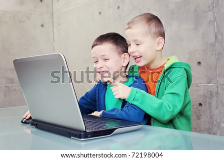 two brothers having fun with laptop - kids and family