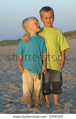 Two brothers holding each other on a beach. Light of the last hour before sunset.