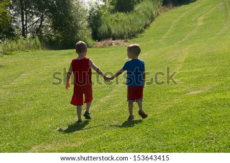 Two brothers holding hands walking along the hill toward the beach on a hot summer day - stock photo