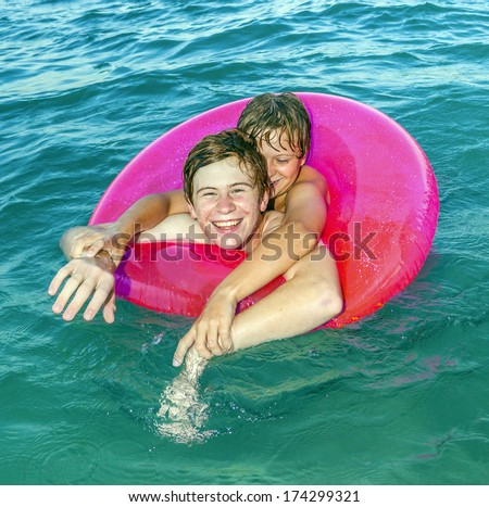 two brothers in a swim ring have fun in the ocean - stock photo