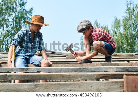 Two brothers in the process of construction of the roof of a barn in the village