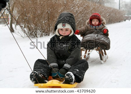 Two brothers in winter day on sled. - stock photo