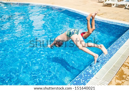 Two brothers jumping into swimming pool