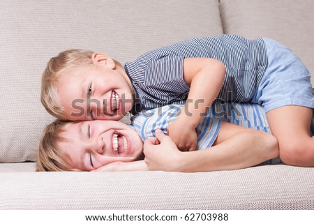 Two brothers laugh, indoor - stock photo