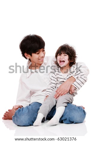 Two brothers laughing together, both are of part Asian - Scandinavian descent. Little brother has cerebral palsy. - stock photo