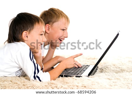 two brothers lie on the carpet with laptop
