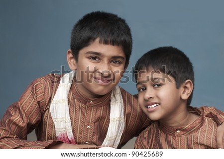 two brothers looking very happy in traditional indian dress - stock photo