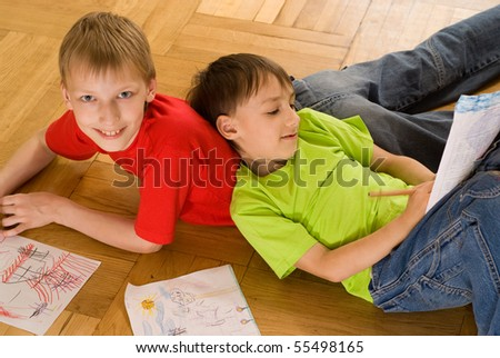 two brothers lying on the floor and draw