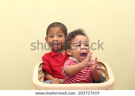 Two brothers of mixed race.  Focus in the front baby. - stock photo