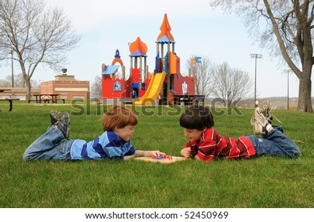 Two brothers play Chinese checkers in the park - stock photo