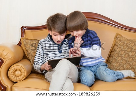 Two brothers play on touchscreen PC - stock photo