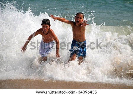 Two brothers playing in the surf at the beach. - stock photo