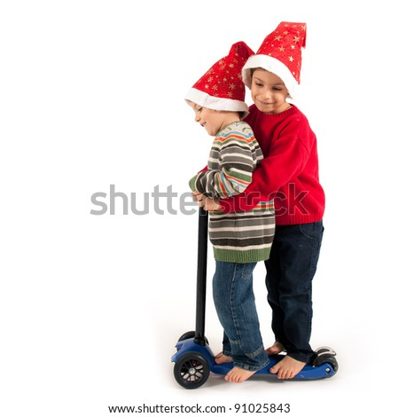 Two Brothers playing together with christmas hat and scooter on white background.
