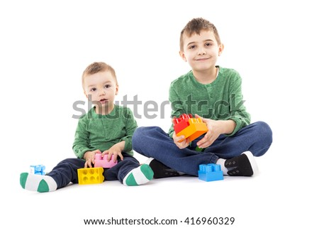 Two brothers playing with colorful cubes on the floor over white - stock photo