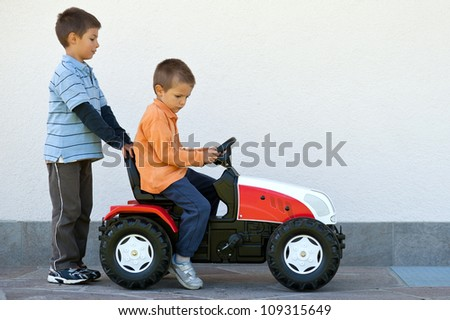 Two brothers playing with tractor toy outdoors. - stock photo