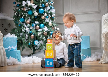 Two brothers playing with wooden alphabet blocks against Christmas tree at home - stock photo