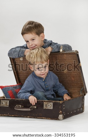 Two brothers posing in studio with luggage - stock photo