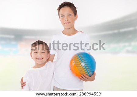 Two brothers posing with ball, smiling. Family portrait.