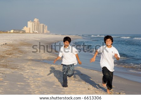 Two brothers racing on the Alabama gulf coast. - stock photo