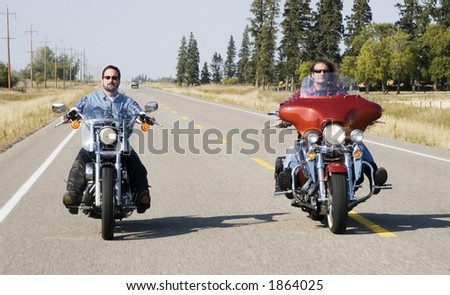 Two brothers ride their motorcycles down the highway.