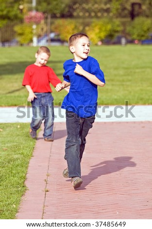 Two brothers run on paths of city park - stock photo