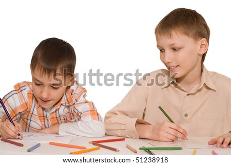 Two brothers sit at the table and draw