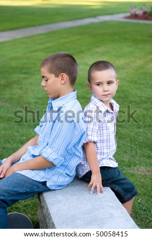 Two brothers sitting back to back on a bench in the park. - stock photo