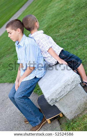 Two brothers sitting back to back on a bench in the park looking very bored. - stock photo