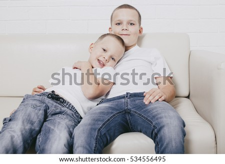 two brothers sitting embracing on the couch. smiling boys reclining on a sofa. watching TV. look at the camera