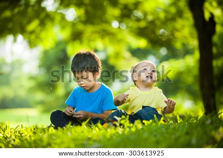 two brothers sitting in green grass