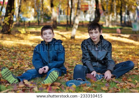 Two brothers sitting on the ground in autumn park - stock photo