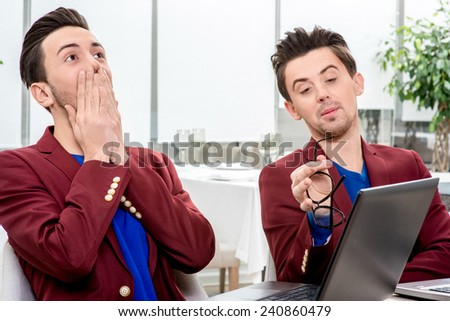 Two brothers twins in red jackets having fun working with laptops and tablet at the office. Family business - stock photo
