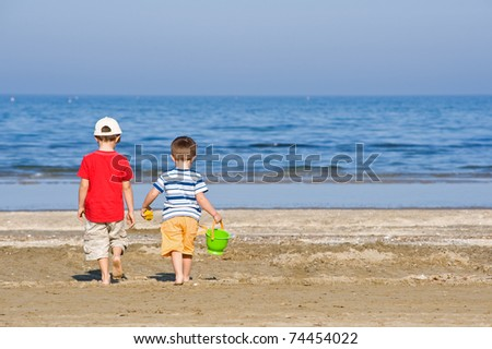 Two brothers walk along the beach in a sunny day. - stock photo