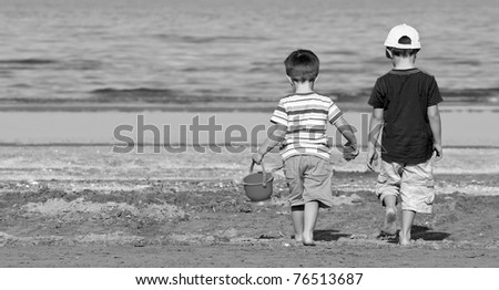 Two brothers walk along the beach in a sunny day. Black and white. - stock photo