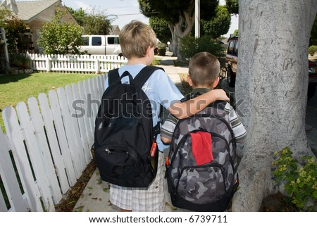 Two brothers walk to school along a white picket fence sidewalk