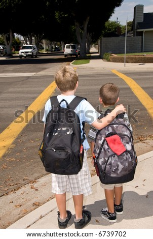 Two brothers walking to school wait at a crosswalk for oncoming traffic