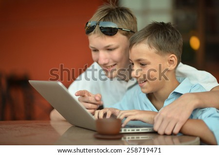 Two brothers with laptop at the table in cafe