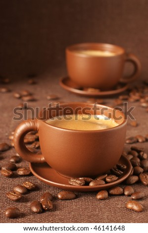 Two brown ceramic cups of coffee with froth and coffee beans on brown canvas.
