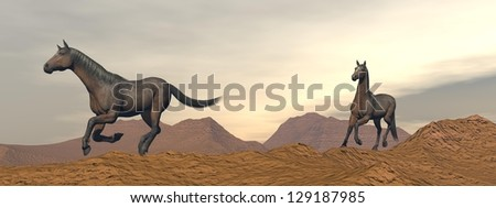 Two brown horses galloping in the desert