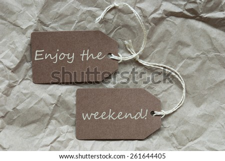 Two Brown Labels Or Tags With White Ribbon On Crumpled Paper Background With English Life Quote Enjoy The Weekend Vintage Or Retro Style - stock photo