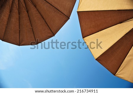Two brown parasols under blue skies. Beach background. View from below. Lying on a sun lounger. - stock photo