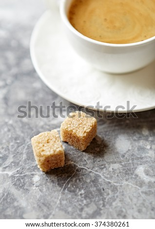 Two brown sugar cubes and a cup of coffee - stock photo