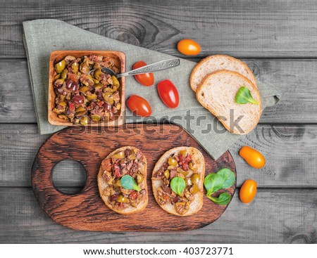 Two bruschetta sandwich with capers, kalamata olives and fresh herbs, cherry tomatoes red, yellow, served on the Board at a gray wooden surface, top view - stock photo