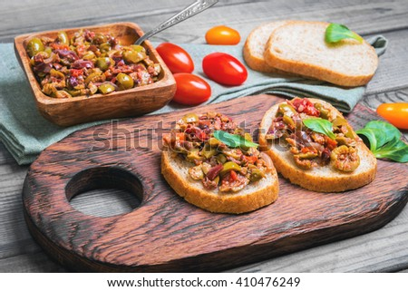 Two bruschetta sandwich with capers, kalamata olives and fresh herbs, cherry tomatoes red, yellow, served on the Board at a gray wooden surface - stock photo