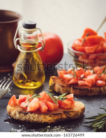 Two bruschettas with fresh tomato and rosemary