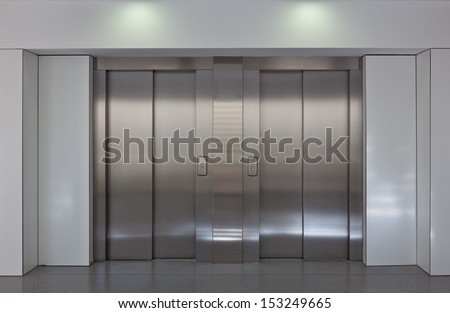 Two brushed metal elevator doors in a minimalistic style building interior  - stock photo