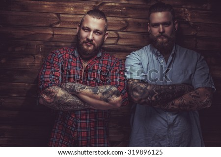 Two brutal mans with beards and tattooes on their hands posing over wooden wall.