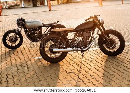 Two brutal vintage custom motorbike caferacer looking in opposite directions on empty rooftop parking lot with backlight sun during sunset. Urban style, hipster lifestyle.