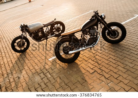 Two brutal vintage custom motorcycle cafe racer looking in opposite directions on empty rooftop parking lot with backlight sun during sunset. Urban style, hipster lifestyle.