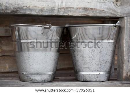 Two buckets in a hut in Pallas-Hetta mountain region in Lapland, Northern Finland. - stock photo